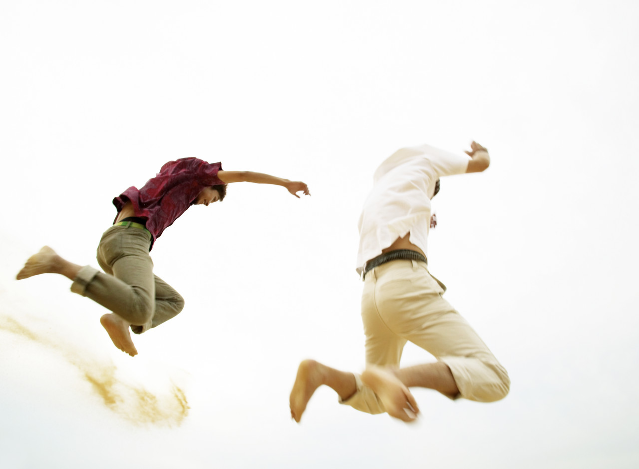 Two Men Jumping in Dunes --- Image by © Royalty-Free/Corbis