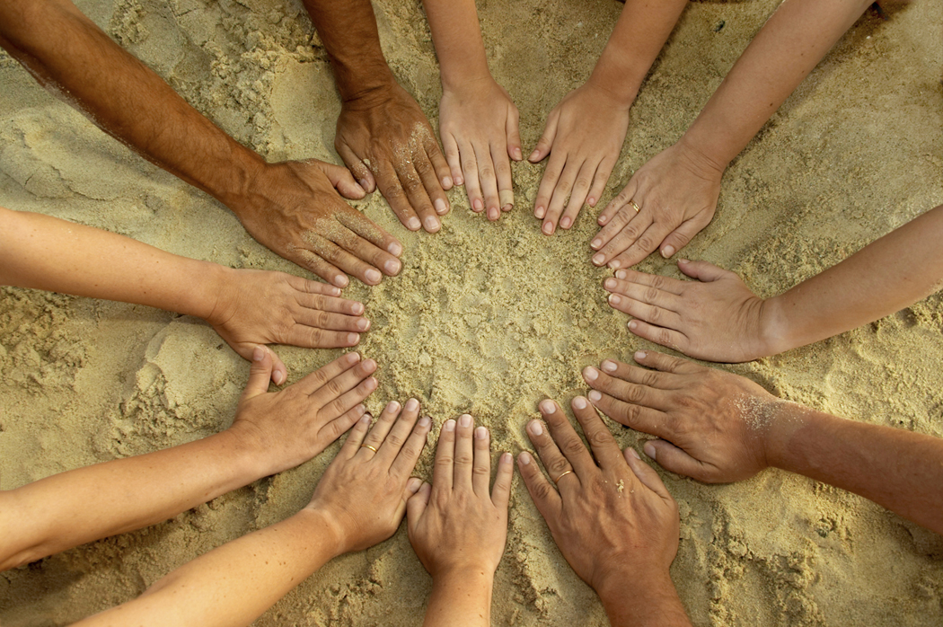 Summer fun. Twelve hands form a circle over the sand. Useful to represent diversity, human nature, teamwork etc. There are male and female hands, different skin colours and ages. Ones have rings and one has a band aid.